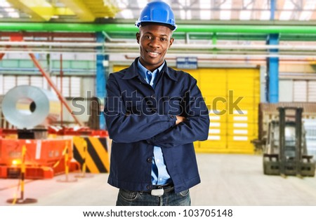 Smiling engineer at work in a factory - stock photo