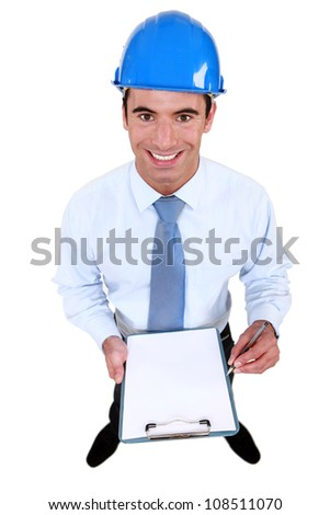 Smiling engineer holding a blank clipboard - stock photo
