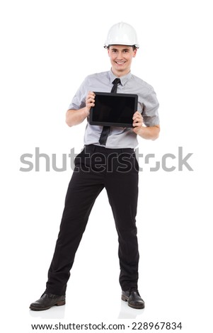 Smiling engineer posing with digital tablet. Full length studio shot isolated on white. - stock photo