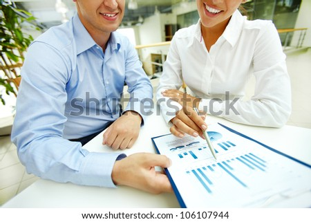 Smiling entrepreneurs being happy with the results of the report - stock photo
