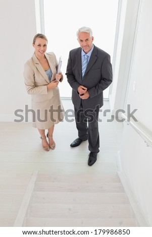 Smiling estate agent standing with potential buyer in empty house