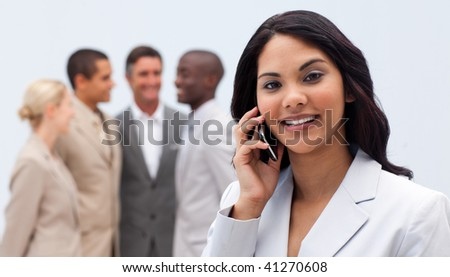 Smiling ethnic businesswoman on phone with her team in the background