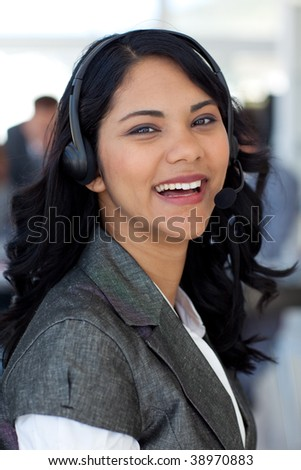Smiling ethnic businesswoman with a headset on in company
