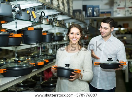 smiling european couple chooses pans in shop cookware