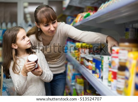 Smiling european female with daughter choosing canned goods in food store