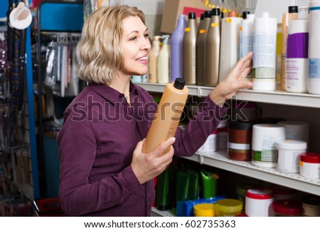 Smiling european mature female customer buying volume shampoo in supermarket hair section