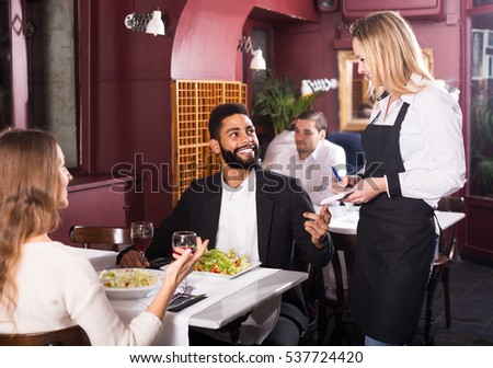 smiling european waitress serving meal for young couple at table