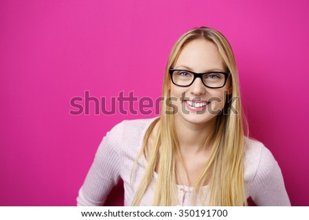 Smiling excited attractive young blond woman wearing black framed glasses leaning towards the camera with a beaming smile over a bright pink magenta background with copy-space - stock photo