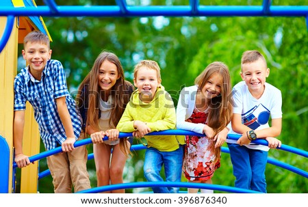 smiling excited kids having fun together on playground - stock photo