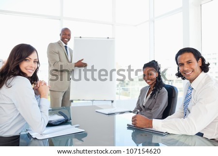 Smiling executive showing a flipchart with his relaxed colleagues - stock photo