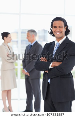 Smiling executive standing upright in front of two colleagues