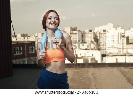 smiling exhausted red haired lady with towel around her neck after workout on roof of high-rise. She wears orange top and blue shorts.  She is slim and fit. weather is sunny. - stock photo