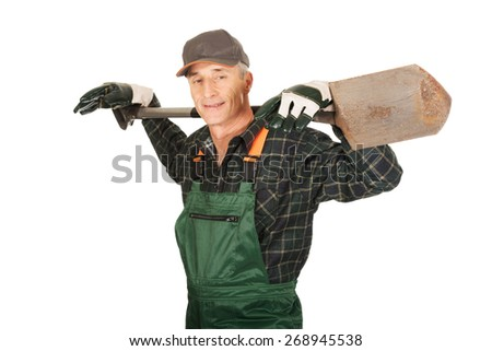 Smiling experienced gardener with a spade on shoulders - stock photo
