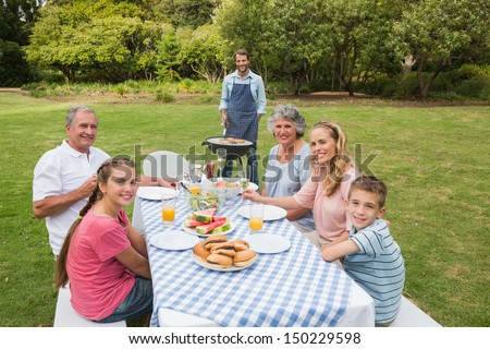 Smiling extended family having a barbecue outside looking at camera - stock photo