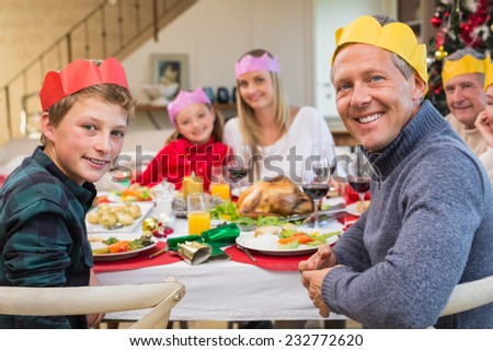 Smiling extended family in party hat at dinner table at home in the living room - stock photo