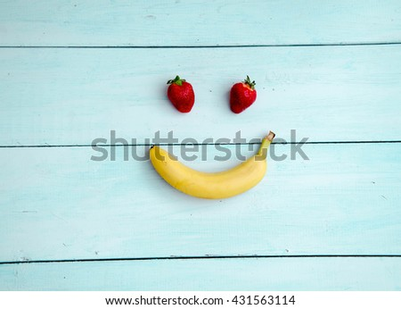 Smiling face made from fruit on a wooden background - stock photo