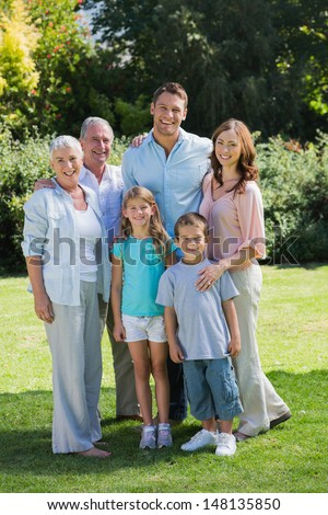 Smiling family and grandparents in the park looking at camera - stock photo