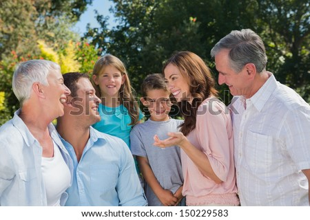 Smiling family and grandparents talking in the park together