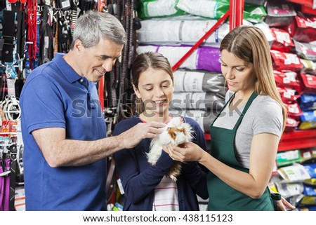 Smiling Family And Saleswoman Looking At Guinea Pig