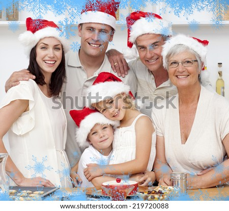 Smiling family baking Christmas cakes against snow flake frame in blue - stock photo