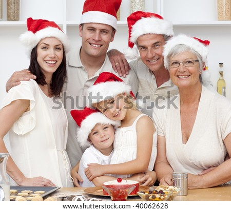 Smiling family baking in kitchen Christmas cakes in the kitchen - stock photo