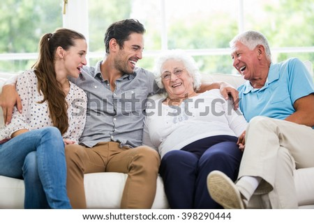 Smiling family discussing while sitting on sofa at home - stock photo