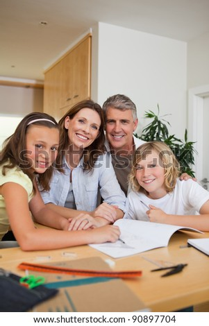 Smiling family doing homework together