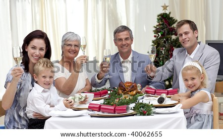 Smiling family drinking a toast in a Christmas dinner at home