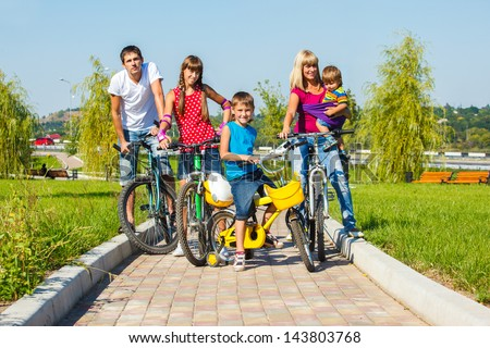 Smiling family enjoying bicycle ride - stock photo