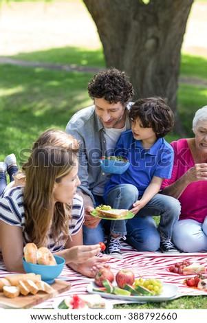 Smiling family having a picnic in the garden - stock photo