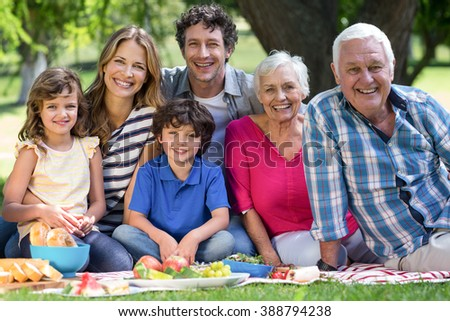 Smiling family having a picnic in the garden - stock photo