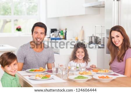 Smiling family having dinner in kitchen - stock photo