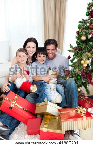 Smiling family having fun with Christmas presents at home - stock photo