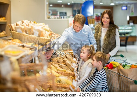 Smiling family in bakery - stock photo