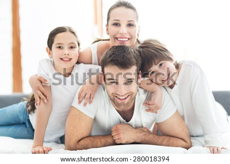 Smiling family in bed - stock photo