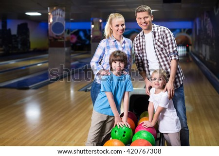 Smiling family in bowling - stock photo