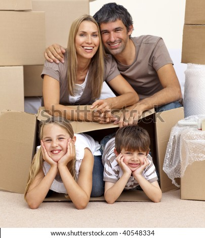 Smiling family in new house playing with boxes