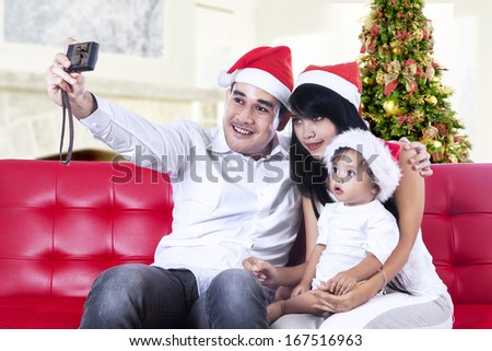 Smiling family in santa hats taking picture with camera