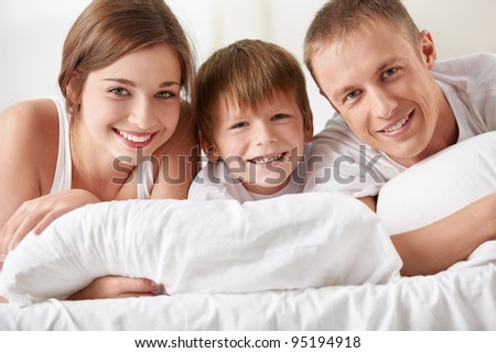 Smiling family in the bedroom - stock photo