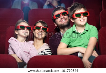 Smiling family in the 3D movie theater - stock photo