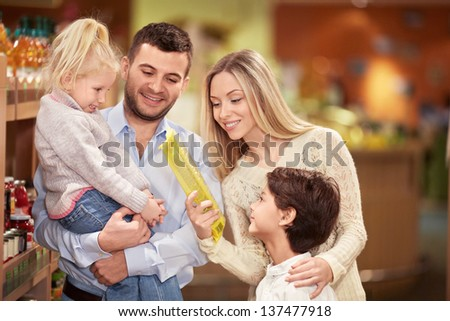 Smiling family in the store - stock photo