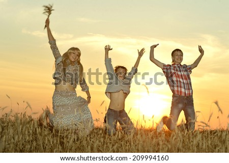 Smiling family jumping in field in evening - stock photo
