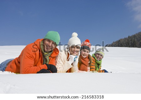Smiling family laying in snow together - stock photo