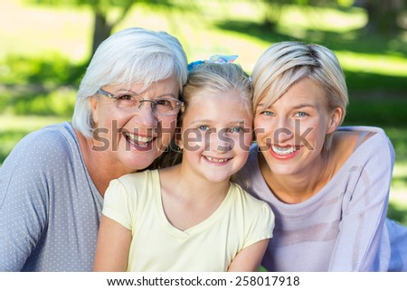 Smiling family looking at the camera on a sunny day - stock photo