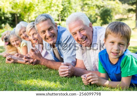 Smiling family looking at the camera with their dog on a sunny day - stock photo