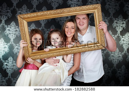 Smiling family looking through an empty frame - stock photo