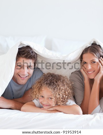 Smiling family lying in bed together - stock photo