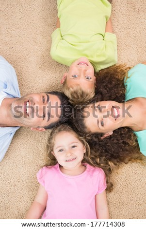 Smiling family lying on the rug in a circle at home in living room - stock photo