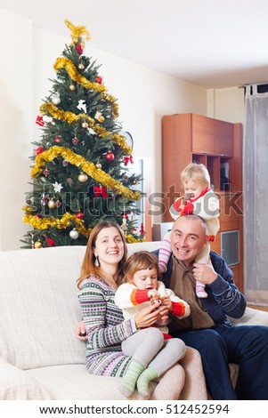 Smiling family of four celebrating Christmas in living room