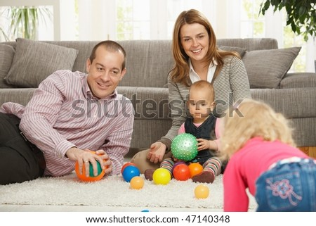 Smiling family of four playing with balls on living room floor.